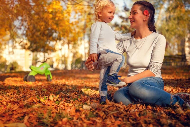 Glückliche Familie - Mutter- und Kinderjunge, der im autu spielt und lacht stockfotos