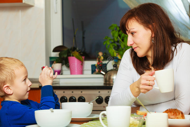Glückliche Familie Mutter- und Sohnjunge scherzen das Kind, das zusammen Frühstück isst stockbilder