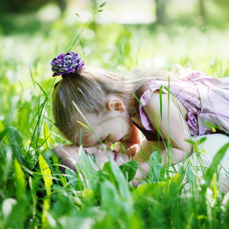 Glückliche Familie Mutter- und Tochterlüge auf einem Gras lizenzfreies stockbild