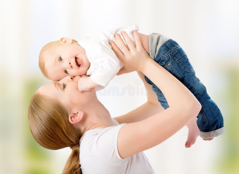 Glückliche Familie. Mutter wirft oben das Baby und spielt stockbilder