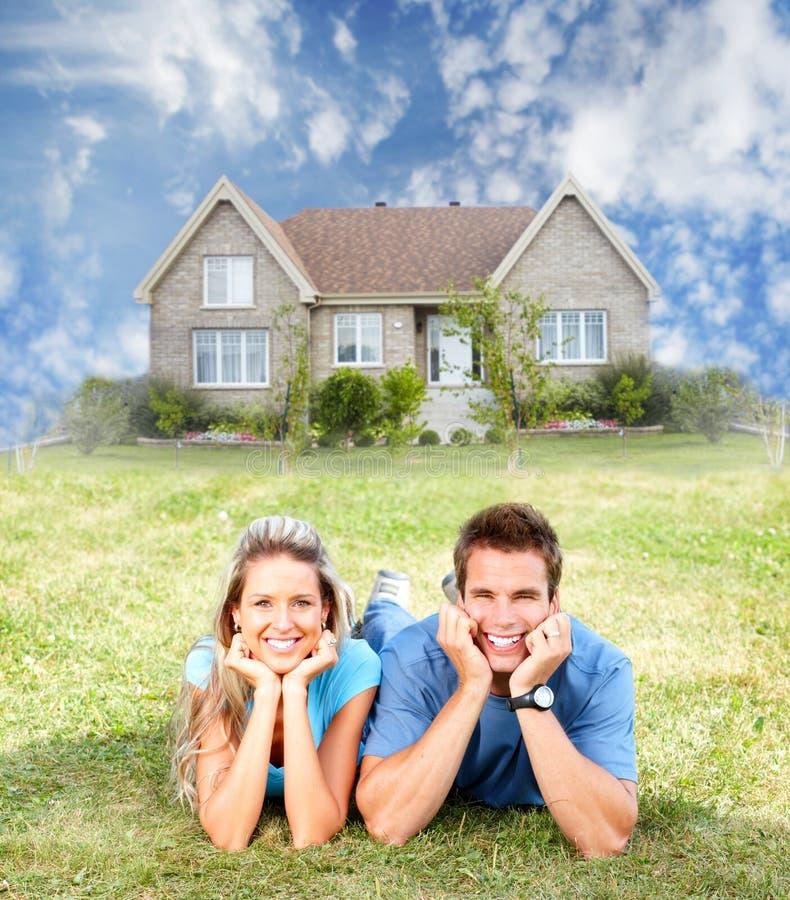 Glückliche Familie nahe neuem Haus. lizenzfreies stockfoto