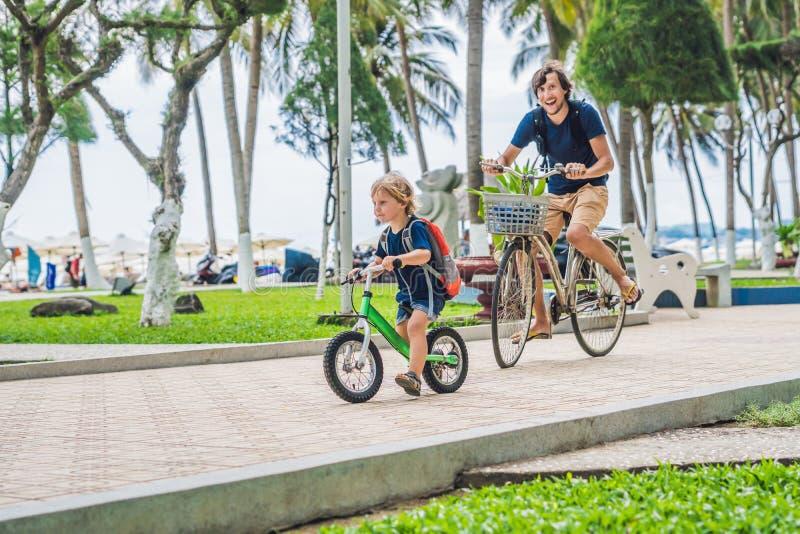 Glückliche Familie reitet Fahrräder draußen und das Lächeln Bringen Sie auf einem Fahrrad und einem Sohn auf einem balancebike he stockbilder