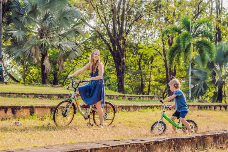 Glückliche Familie reitet Fahrräder draußen und das Lächeln Mutter auf einem Fahrrad und einem Sohn auf einem balancebike stockbilder