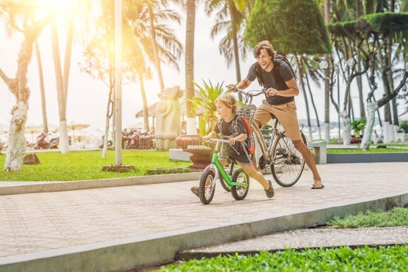 Glückliche Familie reitet Fahrräder draußen und das Lächeln Vater auf einem b lizenzfreie stockfotografie