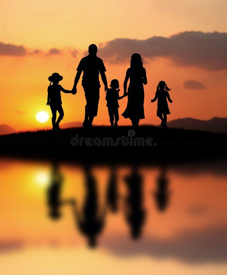Glückliche Familie am Sonnenuntergang lizenzfreie stockbilder
