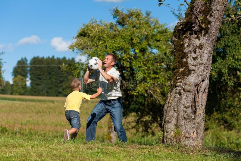 Glückliche Familie spielt Fußball am Sommer lizenzfreie stockfotografie