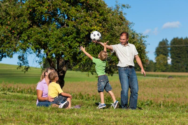 Glückliche Familie spielt Fußball am Sommer stockfotos