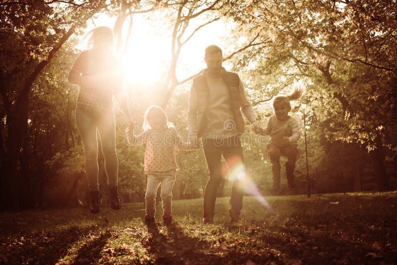Glückliche Familie in springendem Abflussrinnenpark und -Händchenhalten des Parks lizenzfreie stockfotografie