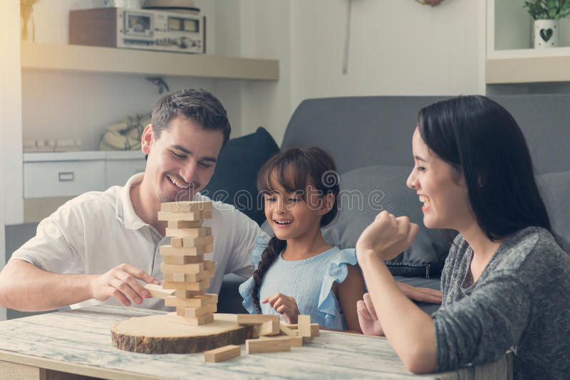 glückliche Familie und die Tochter, welche die Holzklötze spielt, ragen am hom hoch lizenzfreie stockfotografie