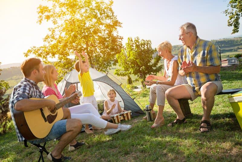 Glückliche Familie und Kinder, die eine Gitarre spielen lizenzfreie stockfotos