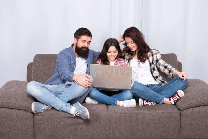 Glückliche Familie unter Verwendung des Laptops Aufenthalt online Kleines Mädchen mit Eltern Mutter und bärtiger Vater mit der To stockfotos