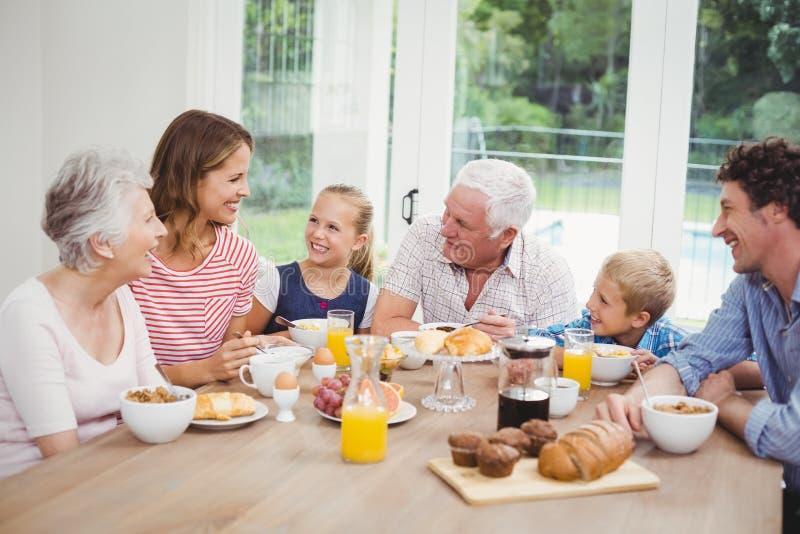 Glückliche Familie von mehreren Generationen, die frühstückt stockbild