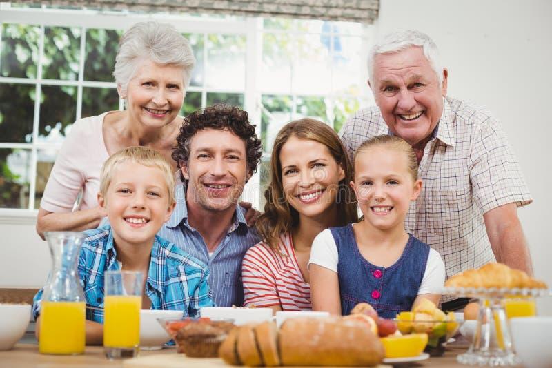 Glückliche Familie von mehreren Generationen durch Frühstückstisch lizenzfreie stockfotografie
