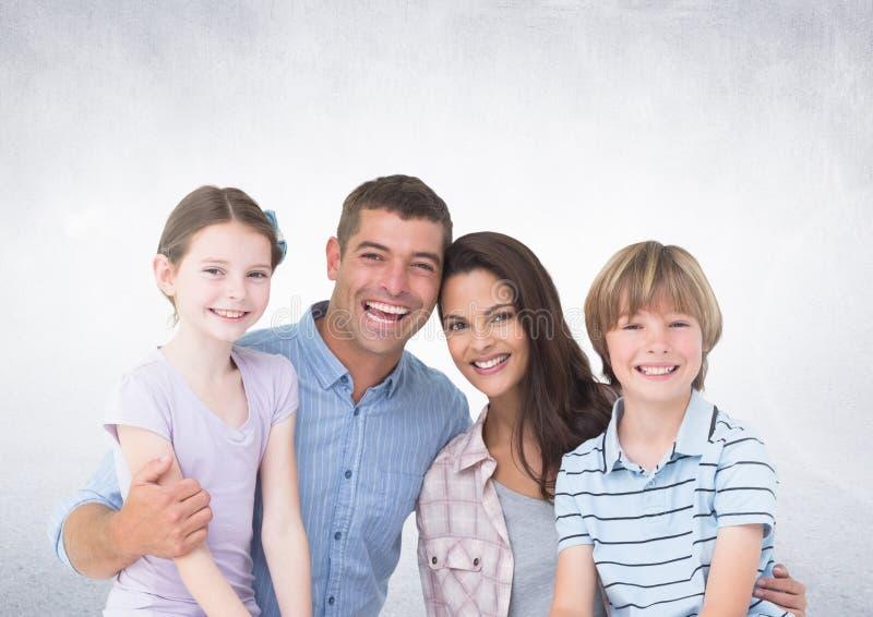 Glückliche Familie vor grauem Hintergrund lizenzfreie stockbilder