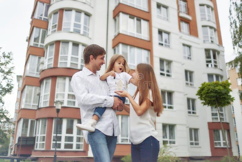 Glückliche Familie vor neuem Wohngebäude stockbilder