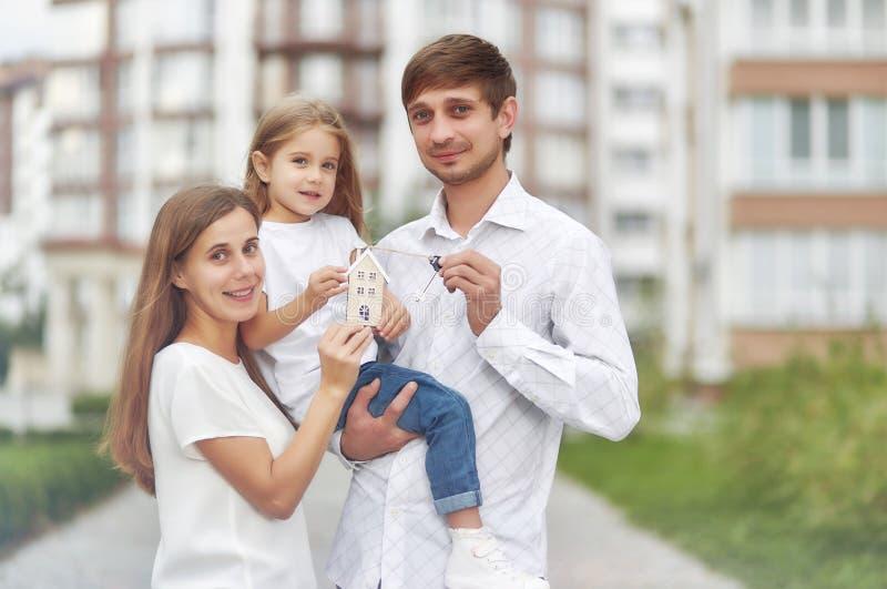 Glückliche Familie vor neuem Wohngebäude stockfoto