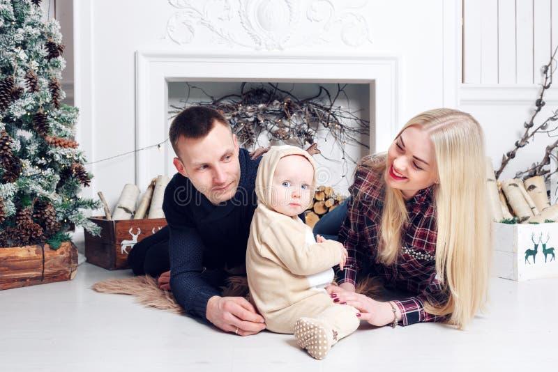 Glückliche Familie am Weihnachten Die Eltern und das Baby, die auf dem Boden und dem Lächeln liegen stockbilder