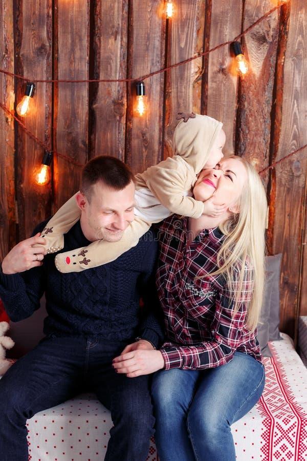 Glückliche Familie am Weihnachten Die Eltern und das Babysitzen Wand von hölzernen Planken und von Girlande lizenzfreies stockbild