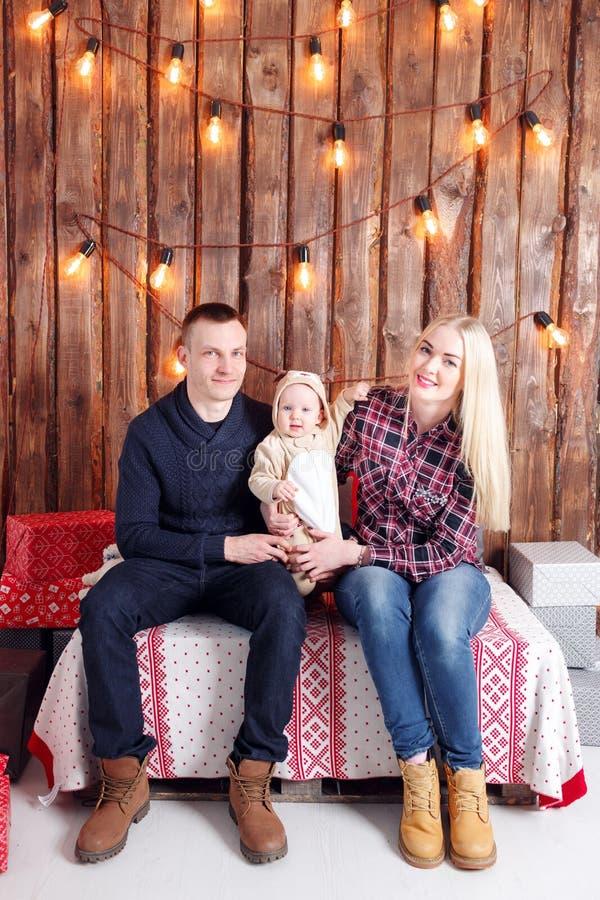 Glückliche Familie am Weihnachten Die Eltern und das Babysitzen Wand von hölzernen Planken und von Girlande stockbild