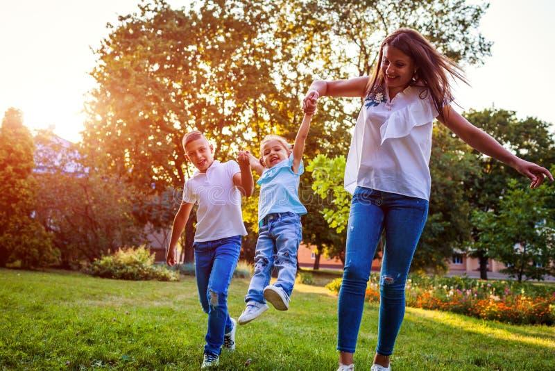 Glückliche Familie, welche die Zeit draußen spielt im Park verbringt Mutter, die Spaß mit zwei Kindern hat Mädchen oben werfen Fa stockfotografie