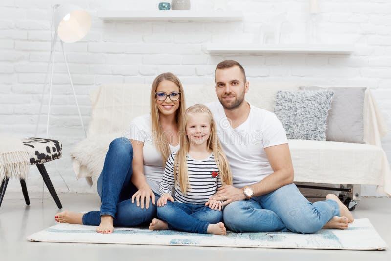 Glückliche Familie zu Hause, die auf Boden sitzt lizenzfreies stockbild