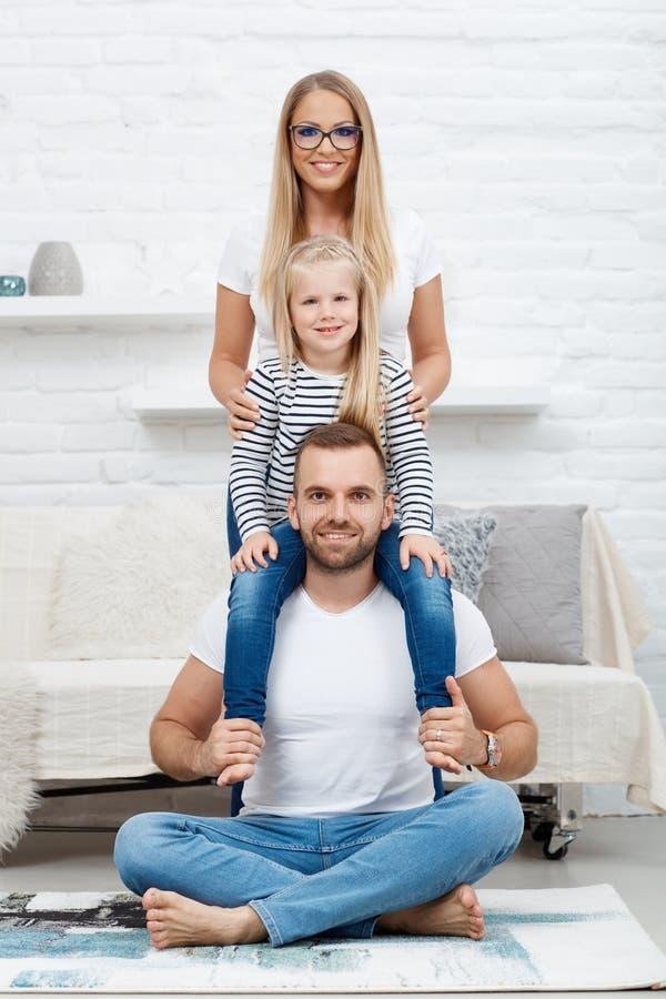 Glückliche Familie zu Hause, die auf Boden sitzt lizenzfreie stockfotografie