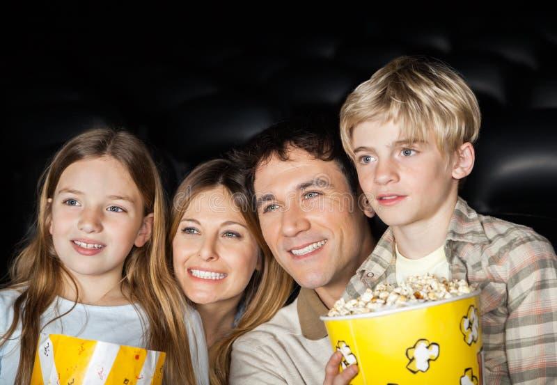 Glückliche Familien-aufpassender Film im Kino stockfotos