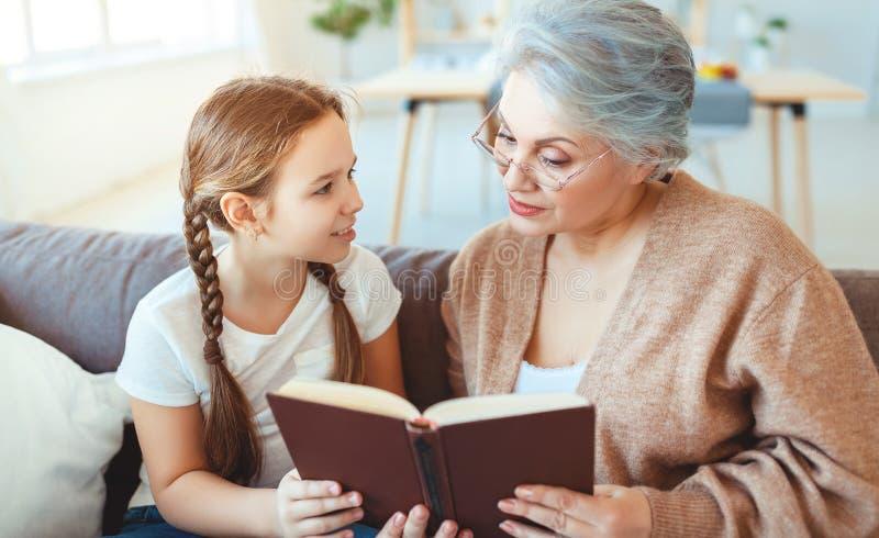 Glückliche Familiengroßmutterlesung zum Enkelinbuch zu Hause stockbilder