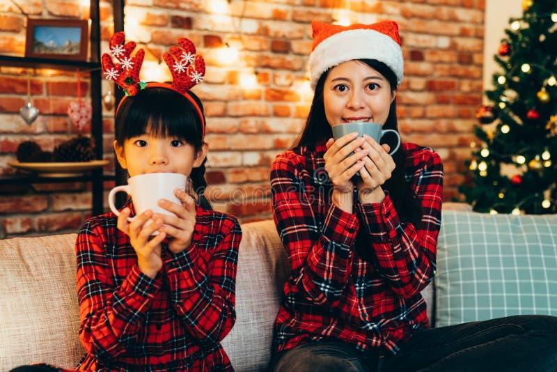 Glückliche Familienholdingschale, die auf Sofa trinkt stockfotos