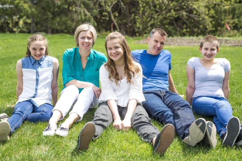 Glückliche Familienmitglieder, die draußen im grünen Gras sitzen stockbilder