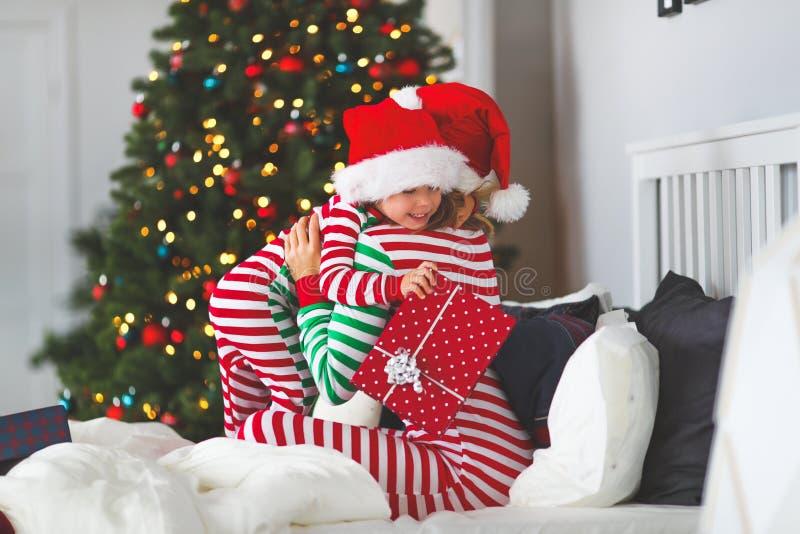 Glückliche Familienmutter ihren Babysohn in den Pyjamas umarmen, die Geschenke O öffnen stockfotografie