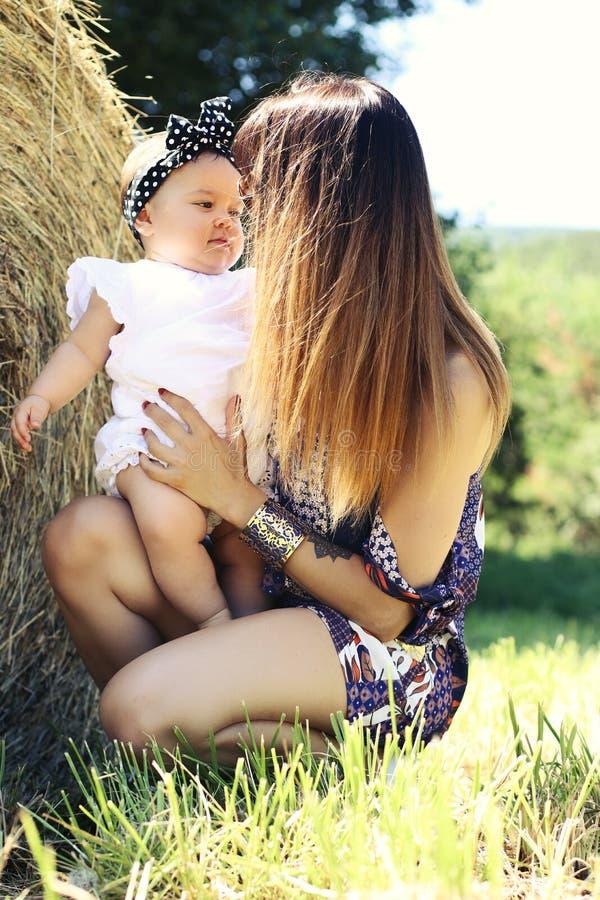 Glückliche Familienmutter und -baby, die in einer Wiese umarmt, blüht lizenzfreies stockbild