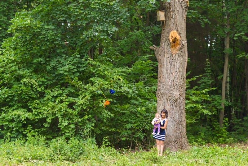 Glückliche Familienmutter und -baby, die im Sommer auf der Natur umarmt lizenzfreies stockbild