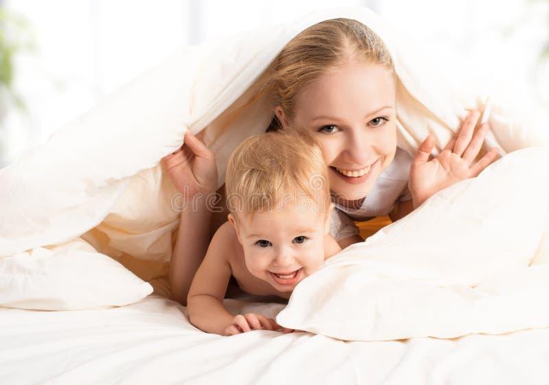 Glückliche Familienmutter und -baby im Bett lizenzfreies stockfoto