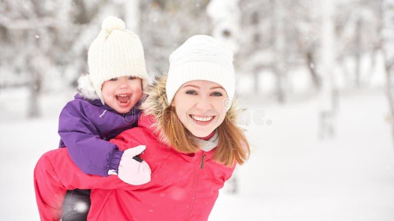 Glückliche Familienmutter und Babytochter, die im Winterschnee spielt und lacht stockfotos