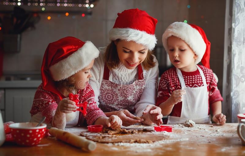 Glückliche Familienmutter und -kinder backen Plätzchen für Weihnachten stockfotografie