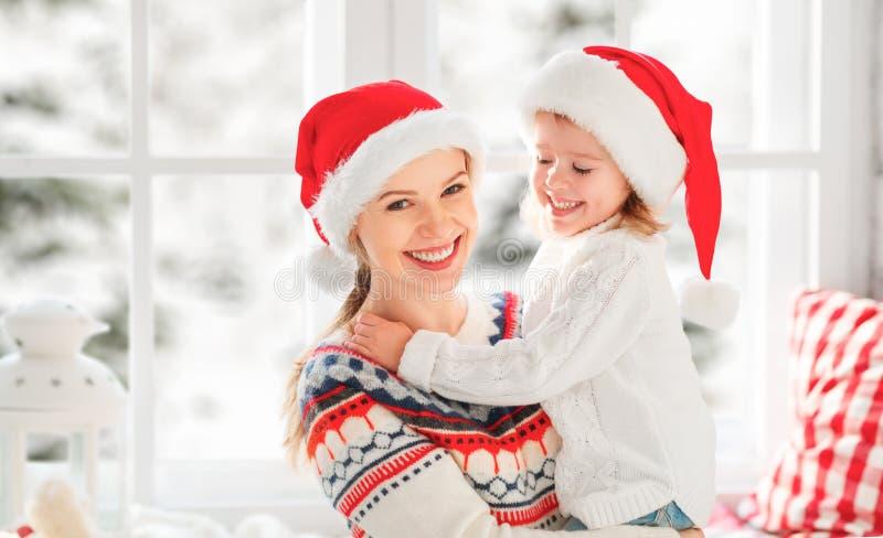 Glückliche Familienmutter und Kindermädchen umarmt am Fenster am Winter stockfotografie