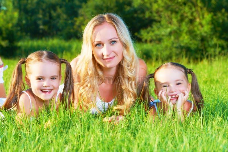 Glückliche Familienmutter und Kinderzwillingsschwestern auf Wiese im Sommer lizenzfreies stockfoto