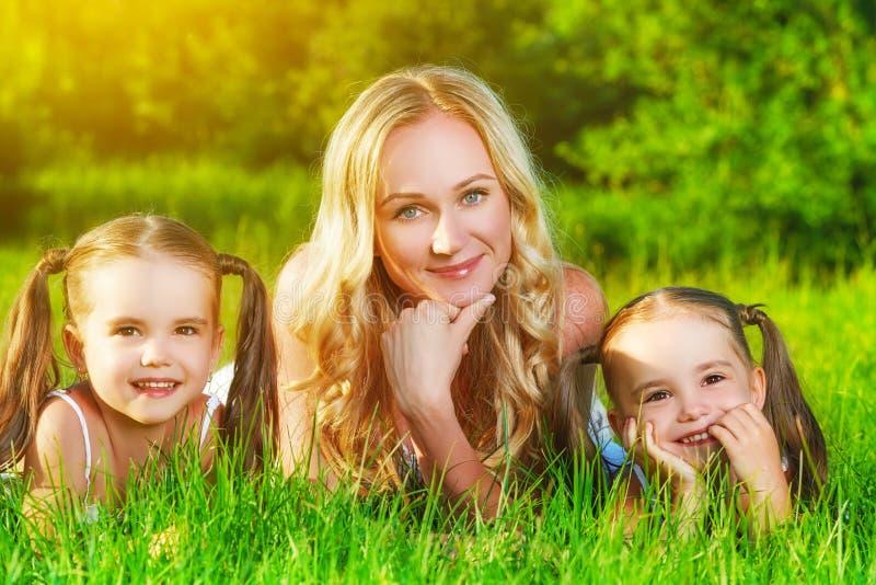 Glückliche Familienmutter und Kinderzwillingsschwestern auf Wiese im summe stockbild