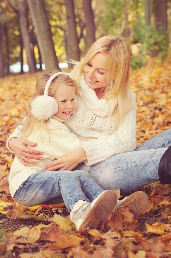 Glückliche Familienmutter und kleine Tochter spielen die Umarmung in Herbstpark stockbild