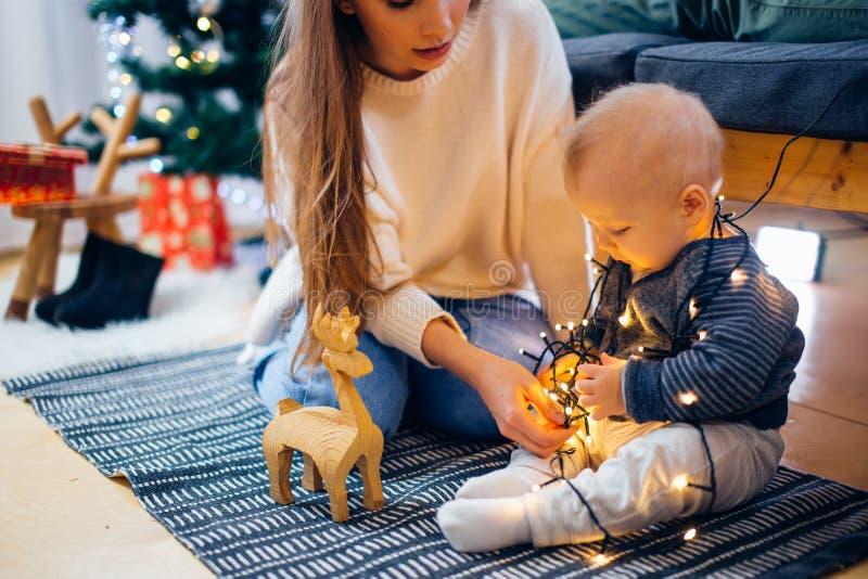 Glückliche Familienmutter und Sohn des Babys kleiner, der nach Hause an den Weihnachtsfeiertagen spielt stockfoto
