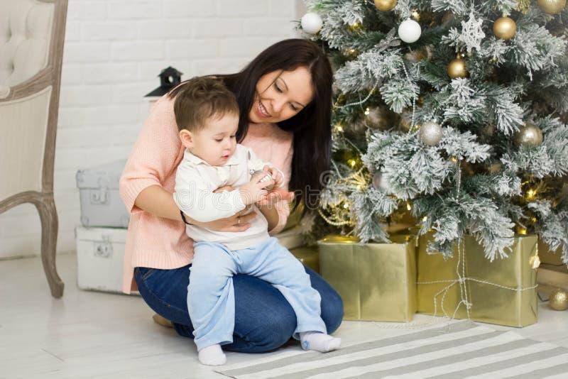 Glückliche Familienmutter und Sohn des Babys kleiner, der nach Hause an den Weihnachtsfeiertagen spielt Neues Jahr ` s Feiertage  lizenzfreies stockbild