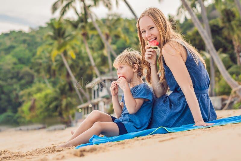 Glückliche Familienmutter und -sohn, die eine Wassermelone auf dem Strand isst Kinder essen gesundes Lebensmittel lizenzfreie stockfotos