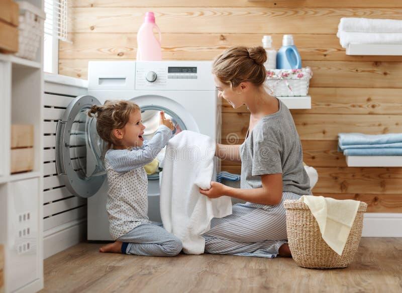 Glückliche Familienmutterhausfrau und -kind in der Wäscherei mit washin lizenzfreies stockfoto