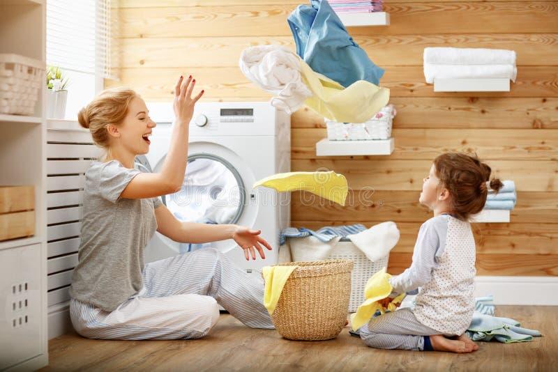 Glückliche Familienmutterhausfrau und -kind in der Wäscherei mit washin stockfoto