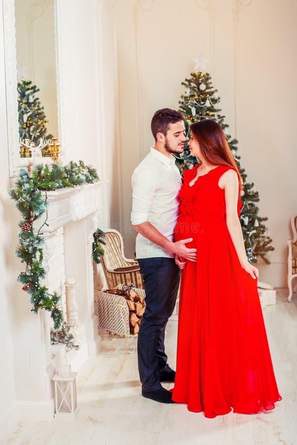 Glückliche Familienpaare auf Weihnachten am Kamin Kuss und Umarmen des glücklichen Paars lizenzfreie stockbilder