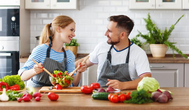 Glückliche Familienpaare, die Gemüsesalat in der Küche zubereiten stockfotos