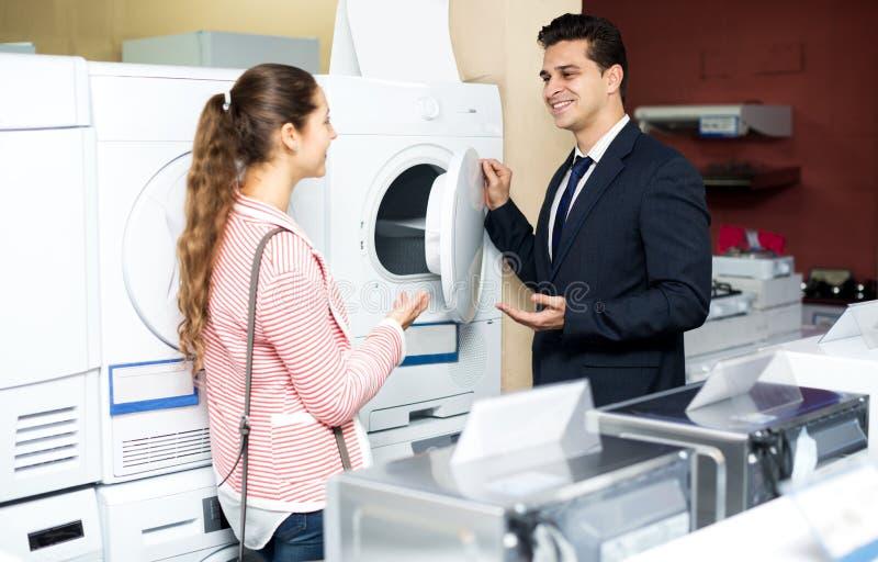 Glückliche Familienpaare, die neue Kleidungswaschmaschine kaufen lizenzfreie stockfotos