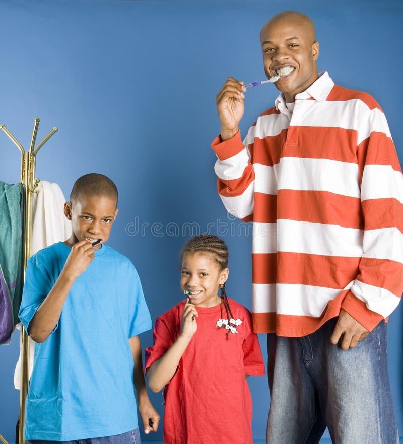 Glückliche Familienreinigungszähne stockfotos