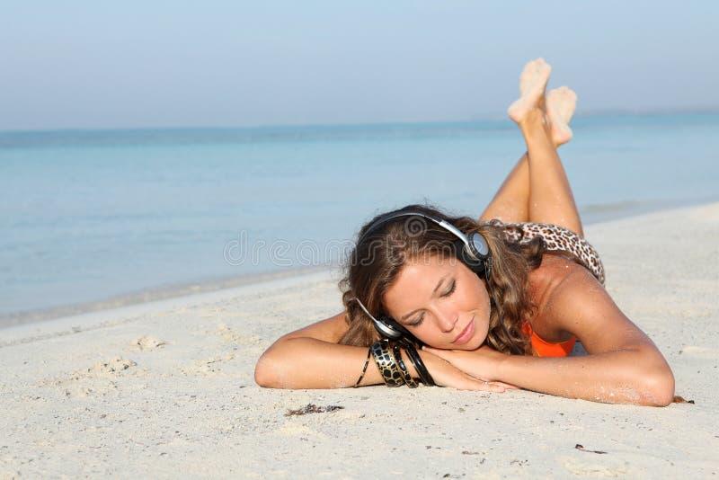 Glückliche Ferienfrau mit Musik auf Kopfhörern lizenzfreies stockfoto